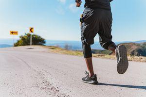 lower body shot of man running on gravel road near coastline