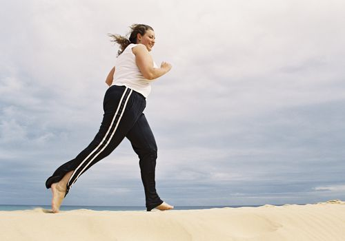 Overweight woman jogging on a beach