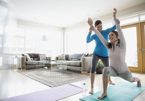 Mujeres haciendo yoga en la sala de estar