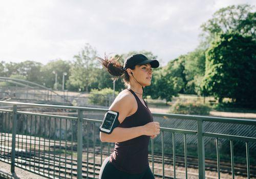 Deportista segura escuchando música a través de auriculares internos mientras trota en el puente en la ciudad