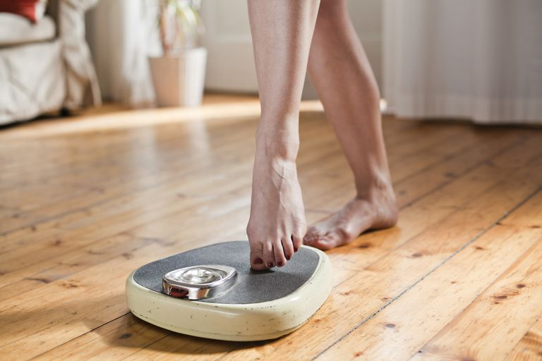 Woman testing personal scales, partial view