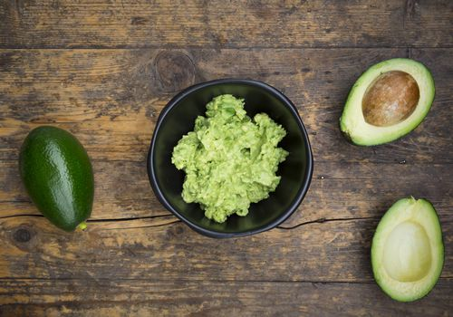 Bowl of Guacamole and whole and sliced avocados on dark wood