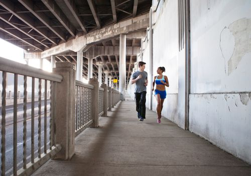 Young couple running on city bridge