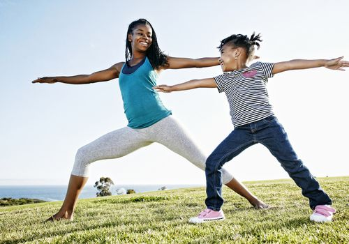 Mother and daughter doing yoga together at a park