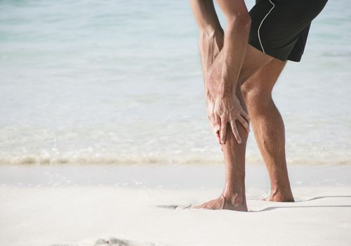 Runner on the beach holding his lower leg in pain