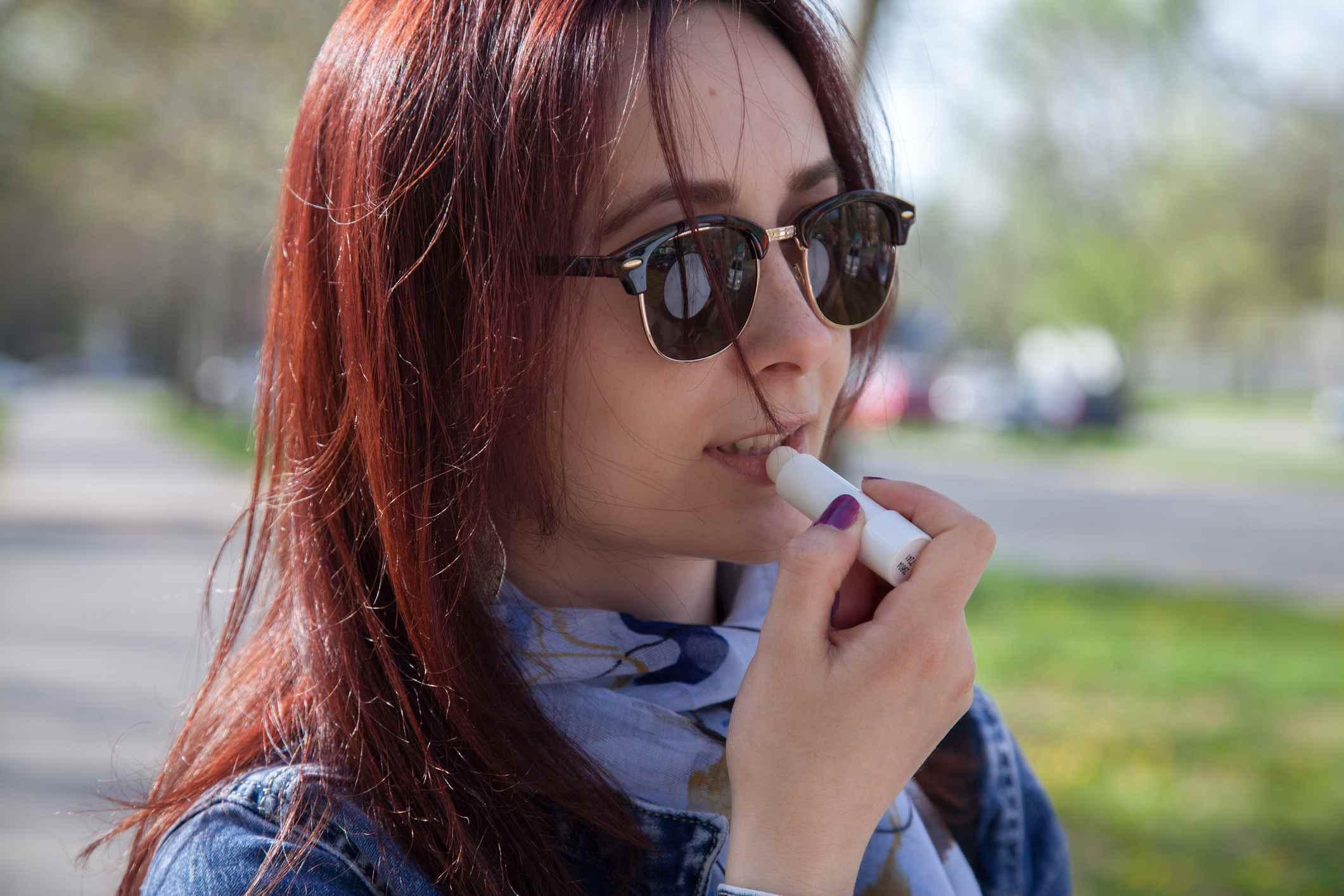 Mujer con gafas de sol aplicando bálsamo labial