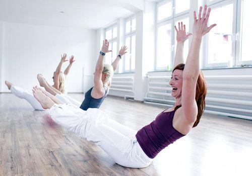 Tres mujeres que se divierten haciendo ejercicios de piso de yoga y Pilates