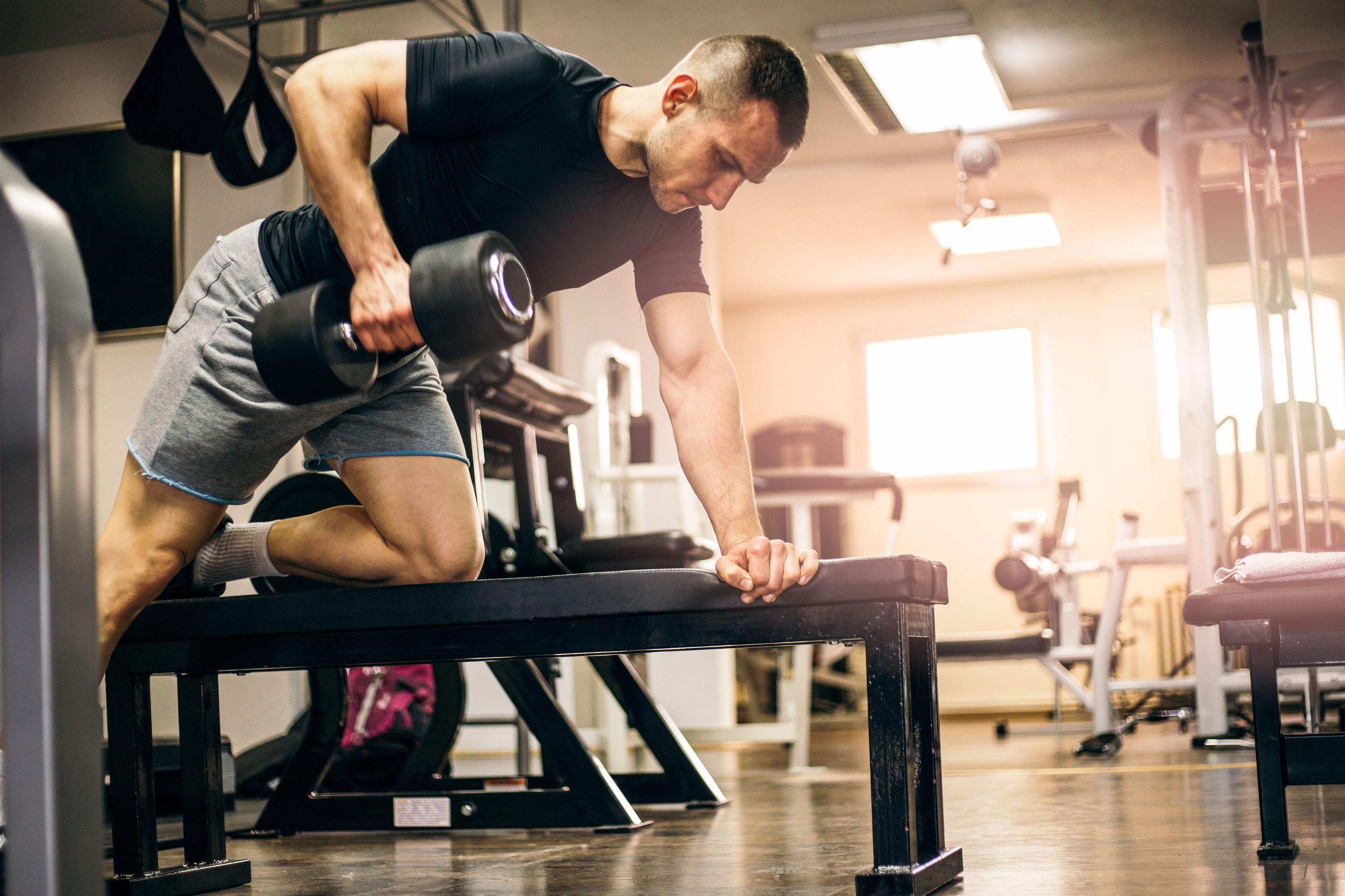 Hombre sano ejercicio con pesas para brazos