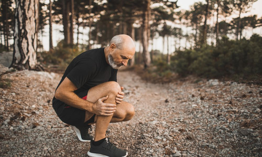 Man with stiff knee while exercising outdoors