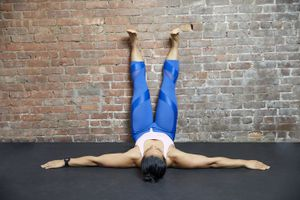 Woman with legs up a brick wall in gym