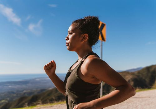 woman jogging in the mountains taking a deep breath