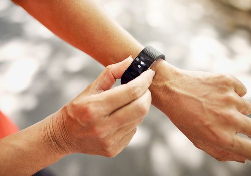 Woman checking a pedometer on her wrist