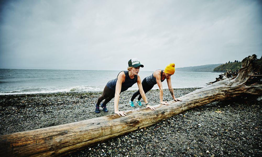 Women doing push ups on log on beach - stock photo