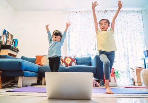 siblings enjoying online yoga class with laptop computer at home