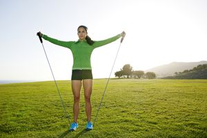 young woman working out with resistance band in park