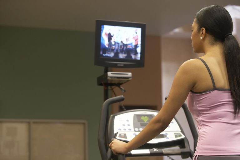 Young woman on treadmill watching television