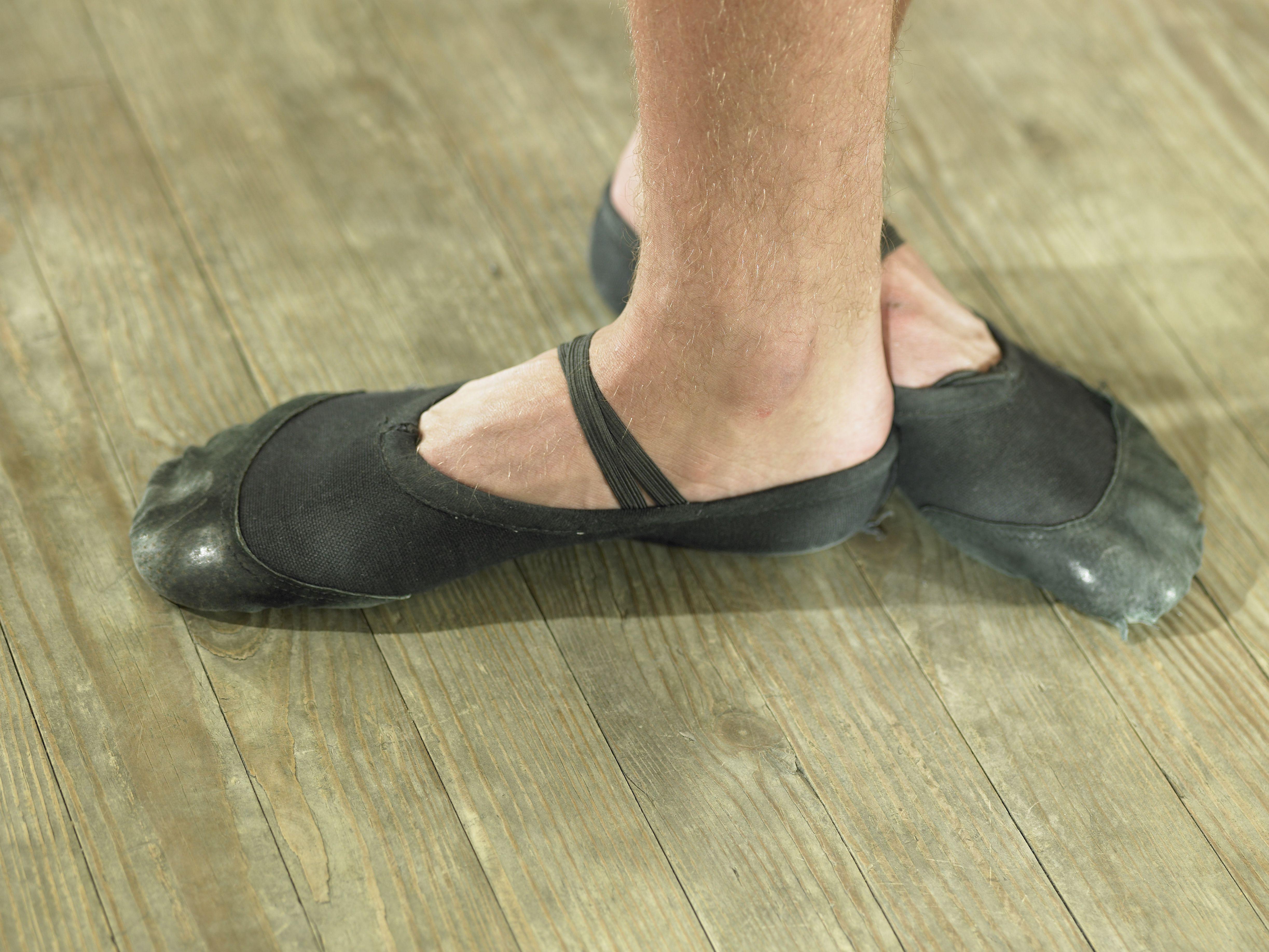 Pies de bailarina de ballet en estudio de danza, primer plano
