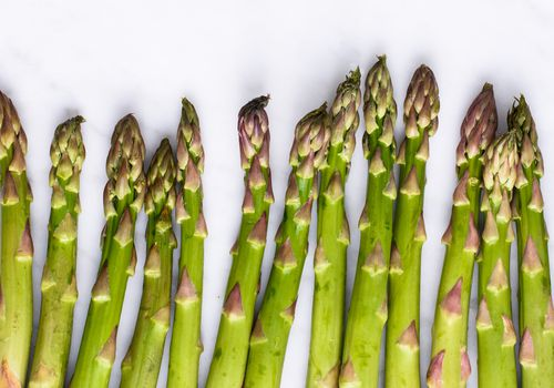 Asparagus stalks on white surface
