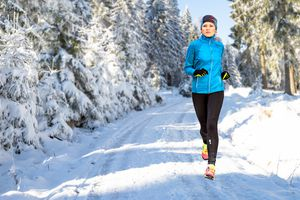 Woman running outdoors in cold weather on snowy path