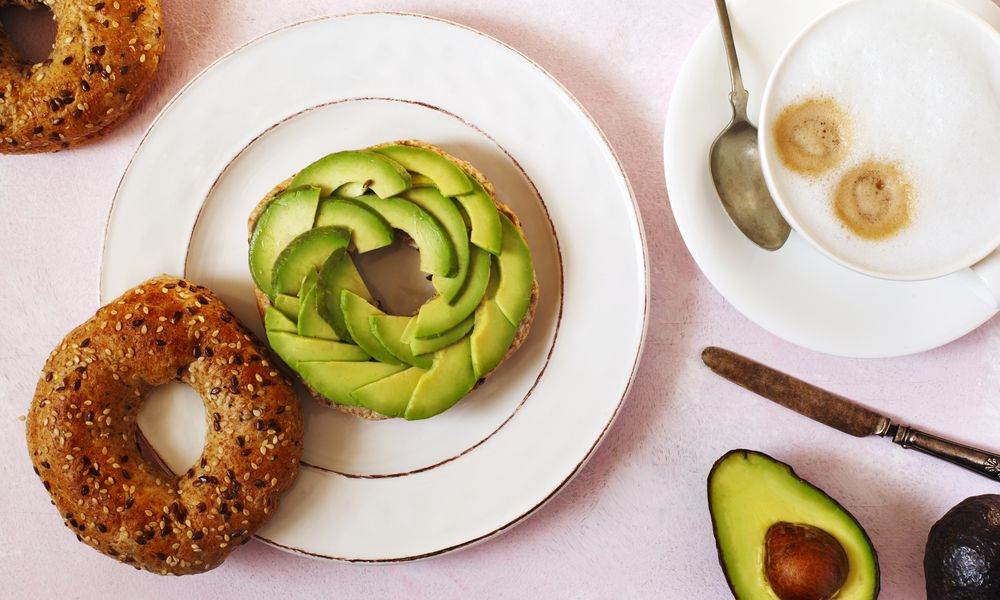 An everything bagel topped with sliced avocados, situated on a white plate next to a latte.
