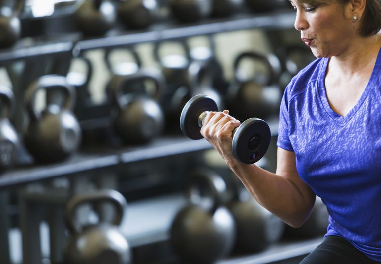 woman sitting in front of rack of kettlebells doing a bicep curl with a dumbbell
