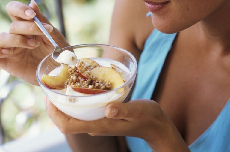woman eating yogurt with fruit