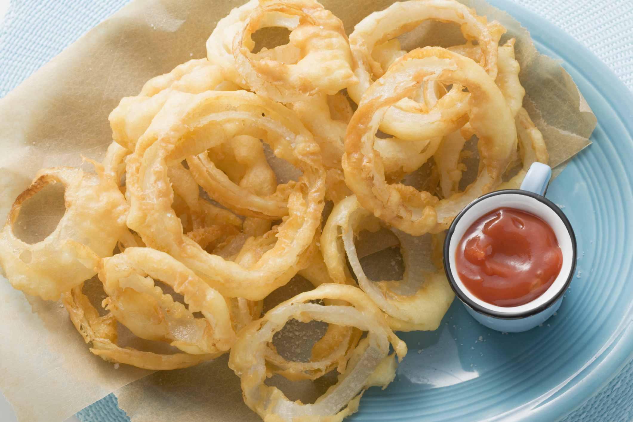 Aros de cebolla en un plato con salsa de tomate