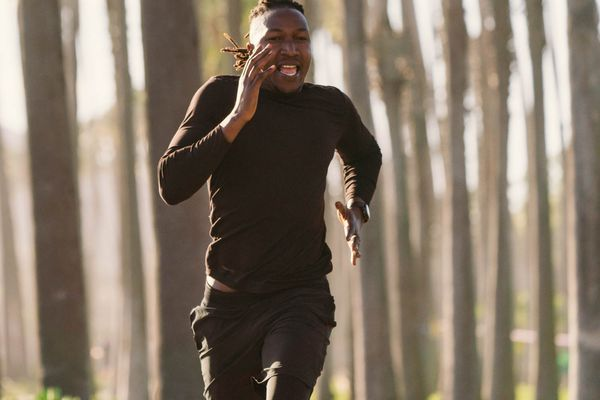 man sprinting while running in the woods
