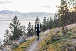 senior woman running on coastal mountain trail