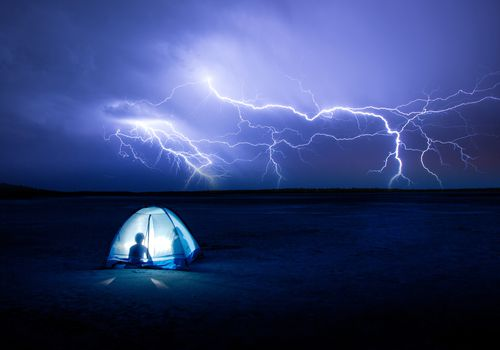 Lightning striking in the distance with two people in a tent in the foreground