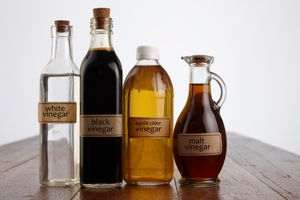 Close-Up Of Various Vinegars On Table Against White Background