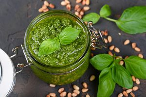 a jar of thick, green pesto made from basil, pine nuts, olive oil, garlic, and cheese