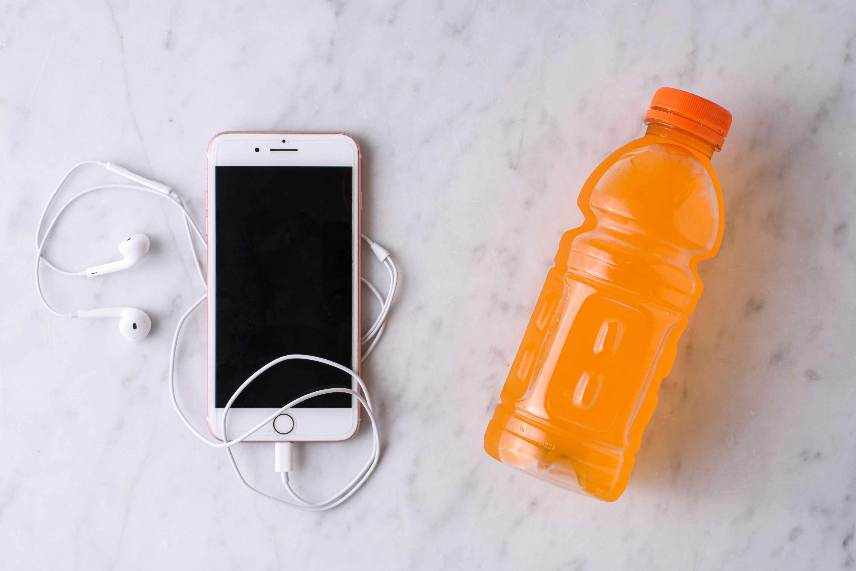 sports drink bottle with iPhone and headphones for exercise