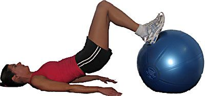 woman performing hamstring roll on a ball