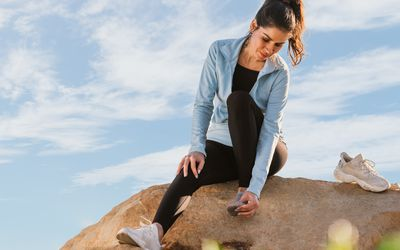 woman sitting on a rock with foot pain