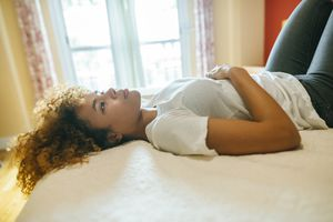 Thoughtful young woman with curly hair lying in bed at home