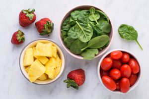 fruits and vegetables including strawberries, pineapple, spinach, and tomato