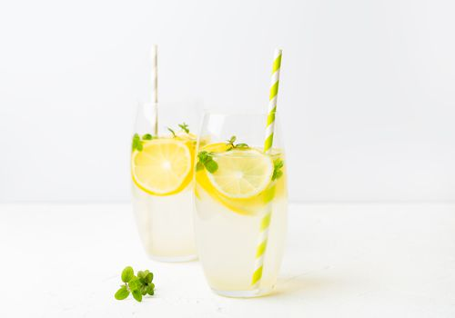 Two ice water glasses with lemons and yellow straws.