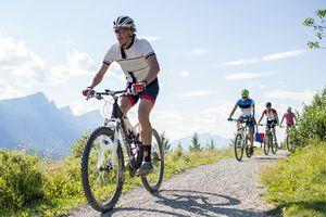Mountain bikers race along mountain pathway