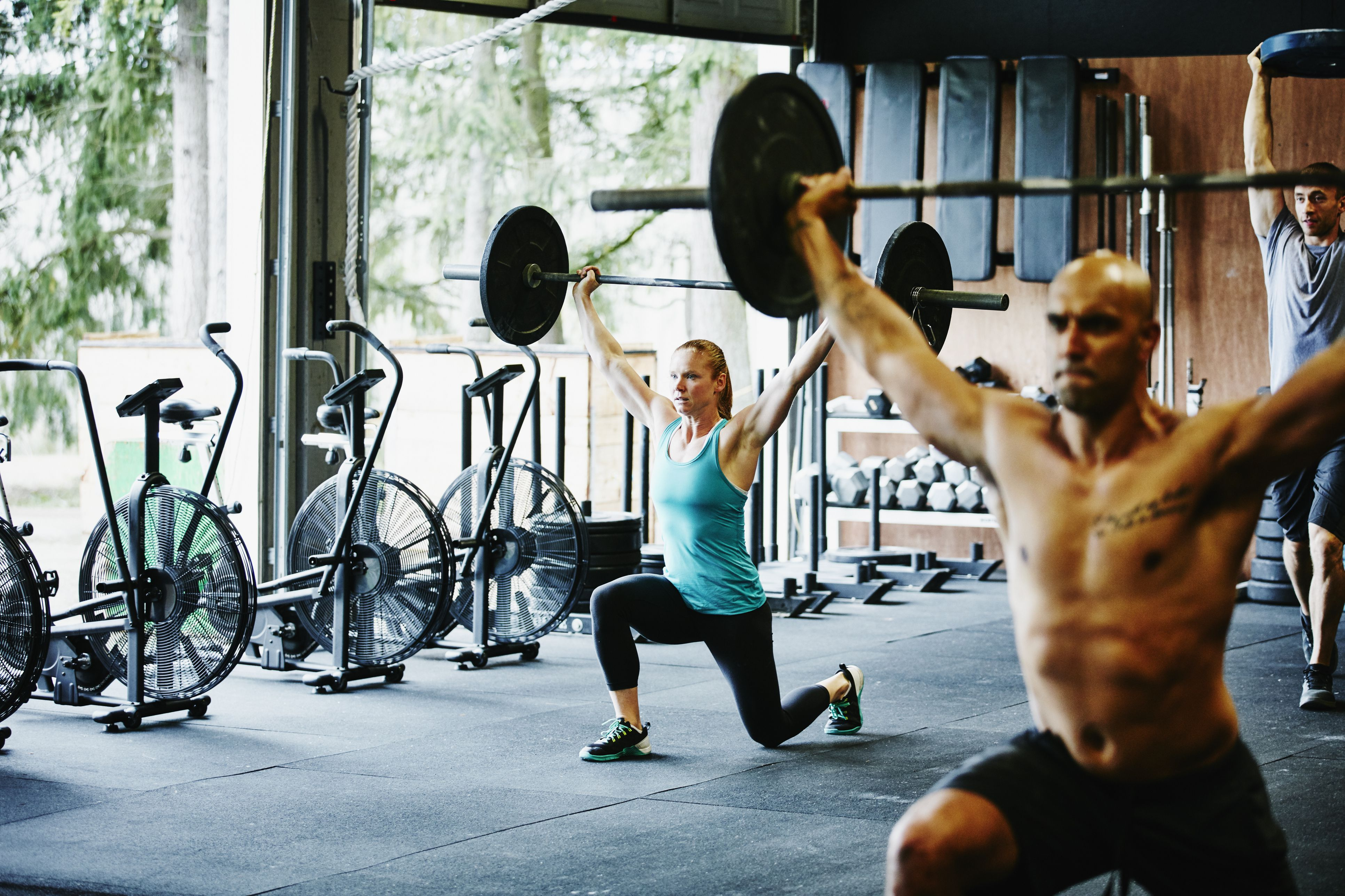 Woman doing barbell walking lunges with friends