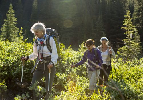 Three women hike through mountain meadow