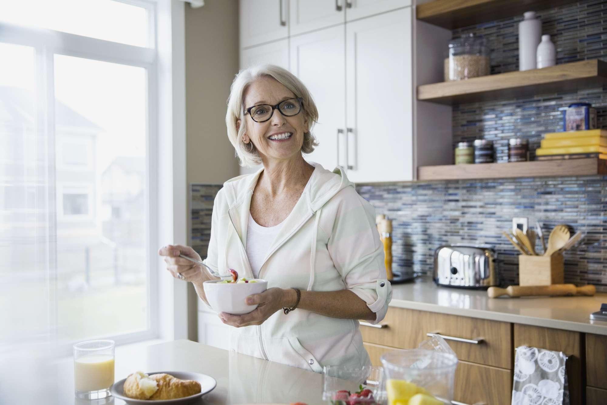 Smiling woman eating fruit salad in kitchen