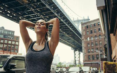 Woman stretching under bridge