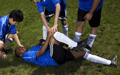 Soccer player down on the field holding his knee in pain