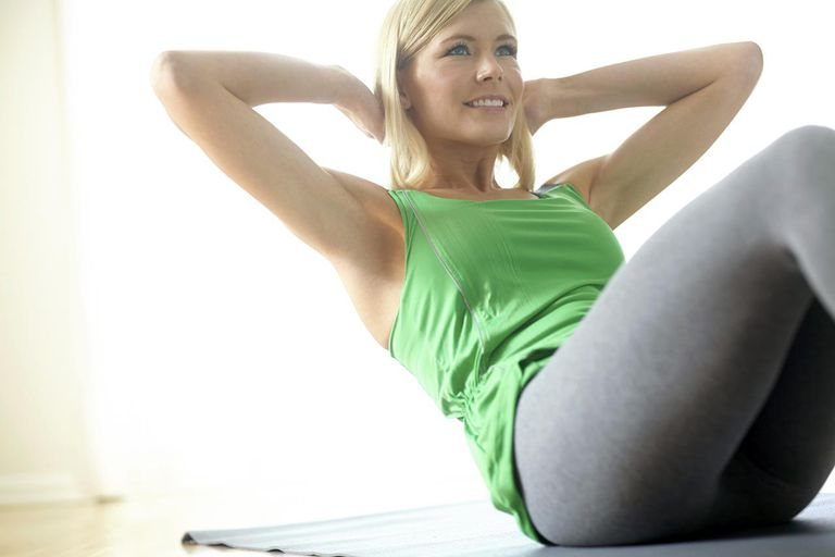 Attractive young blonde woman exercising at home