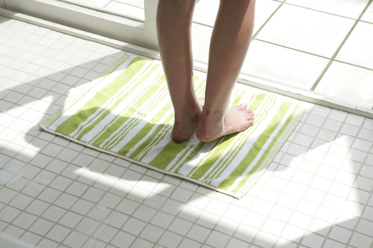 Low section view of a woman's feet on a bathroom floor