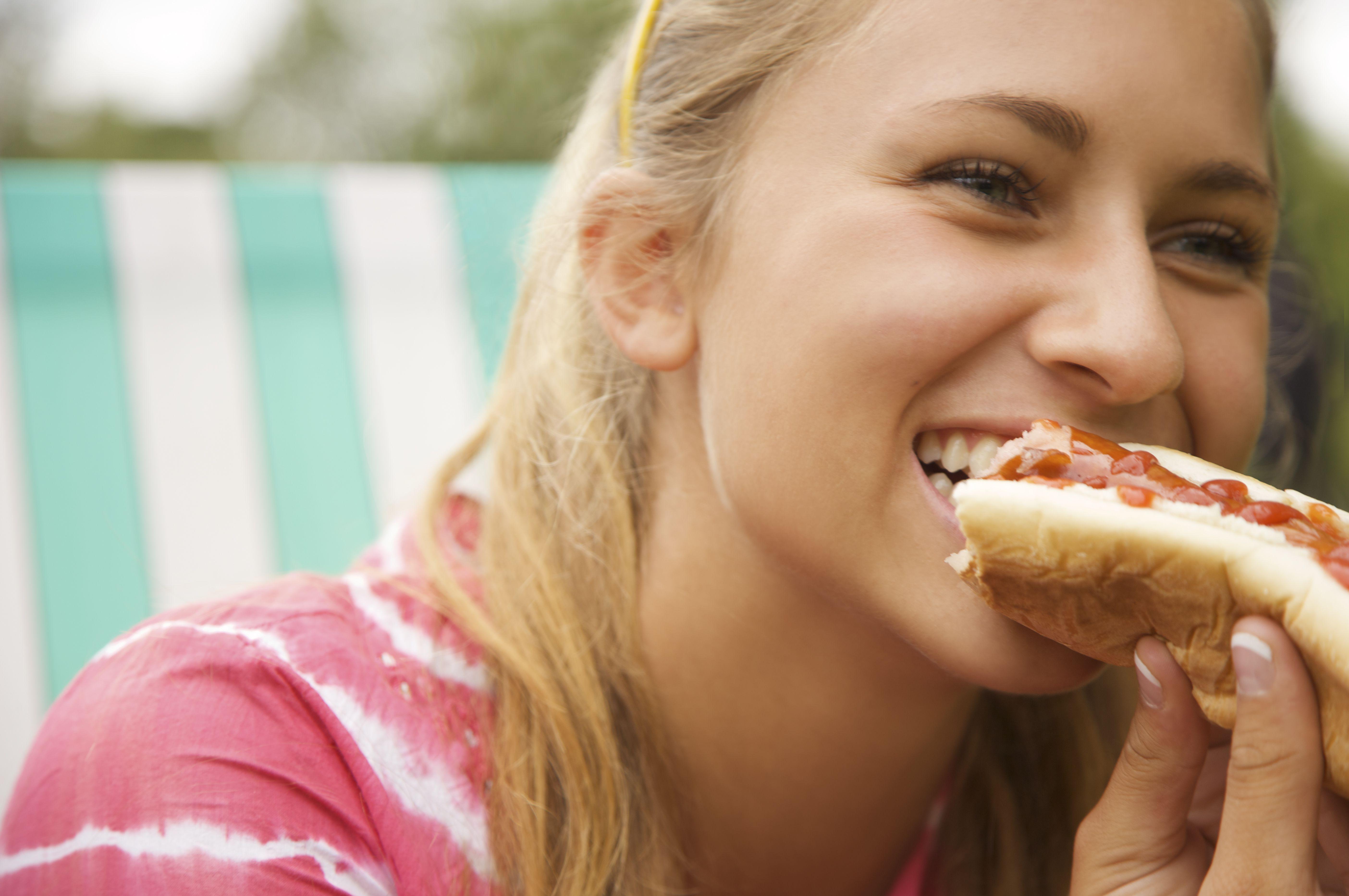 Close up of a teenaged girl eating a hot dog