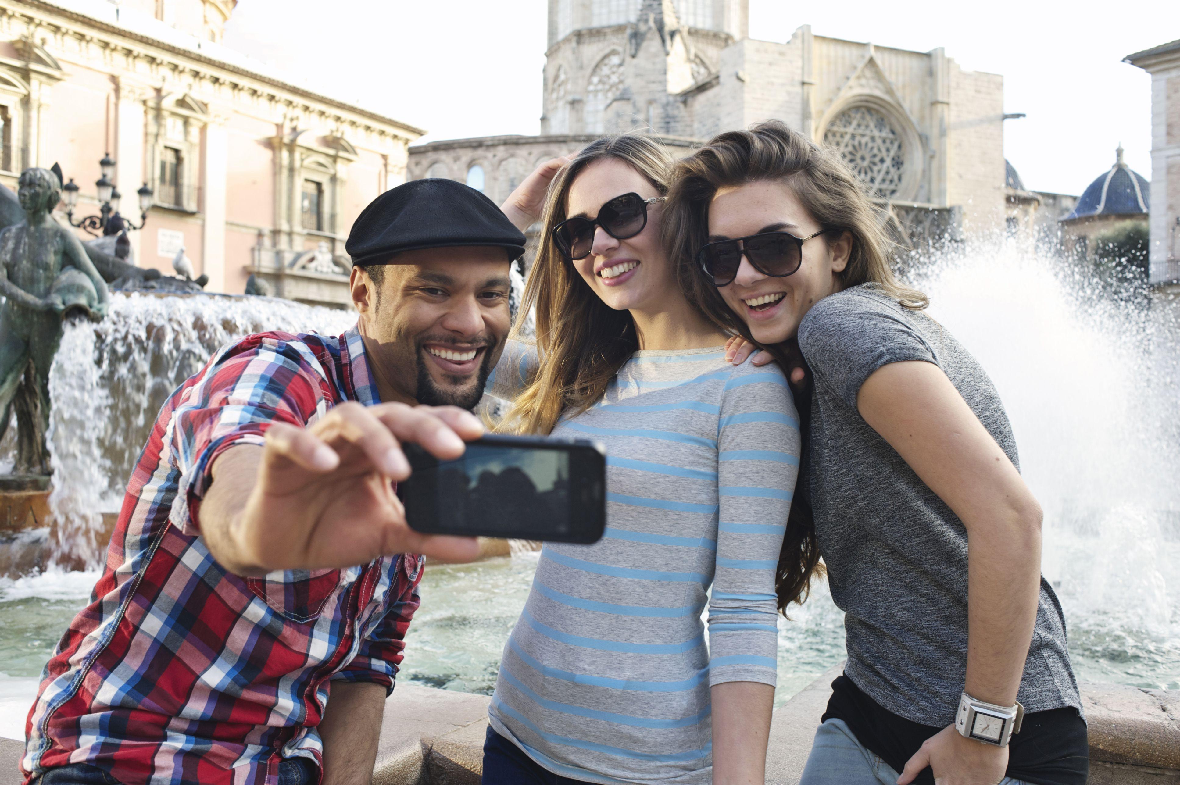 dos mujeres y un hombre tomando un selfie frente a una fuente