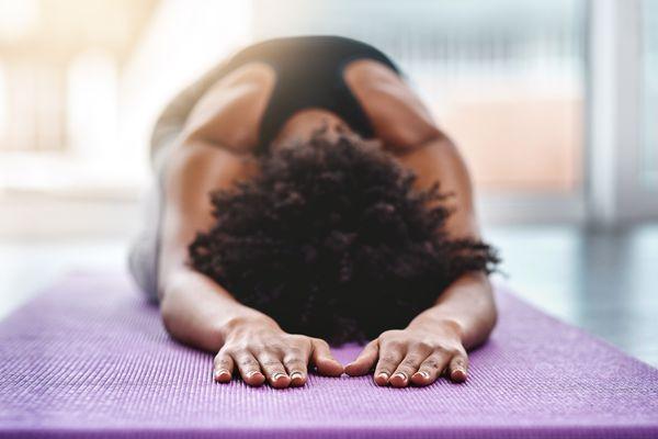 Portrait shot of a woman doing yoga in a studio.