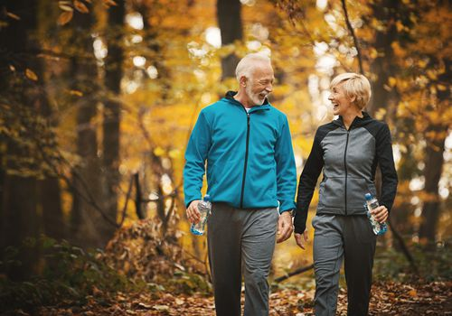 Senior couple walking in autumn forest
